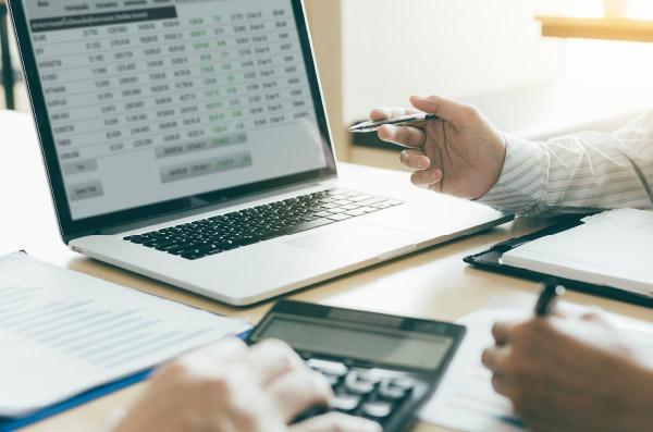 Steuerberatung am Laptop mit Taschenrechner